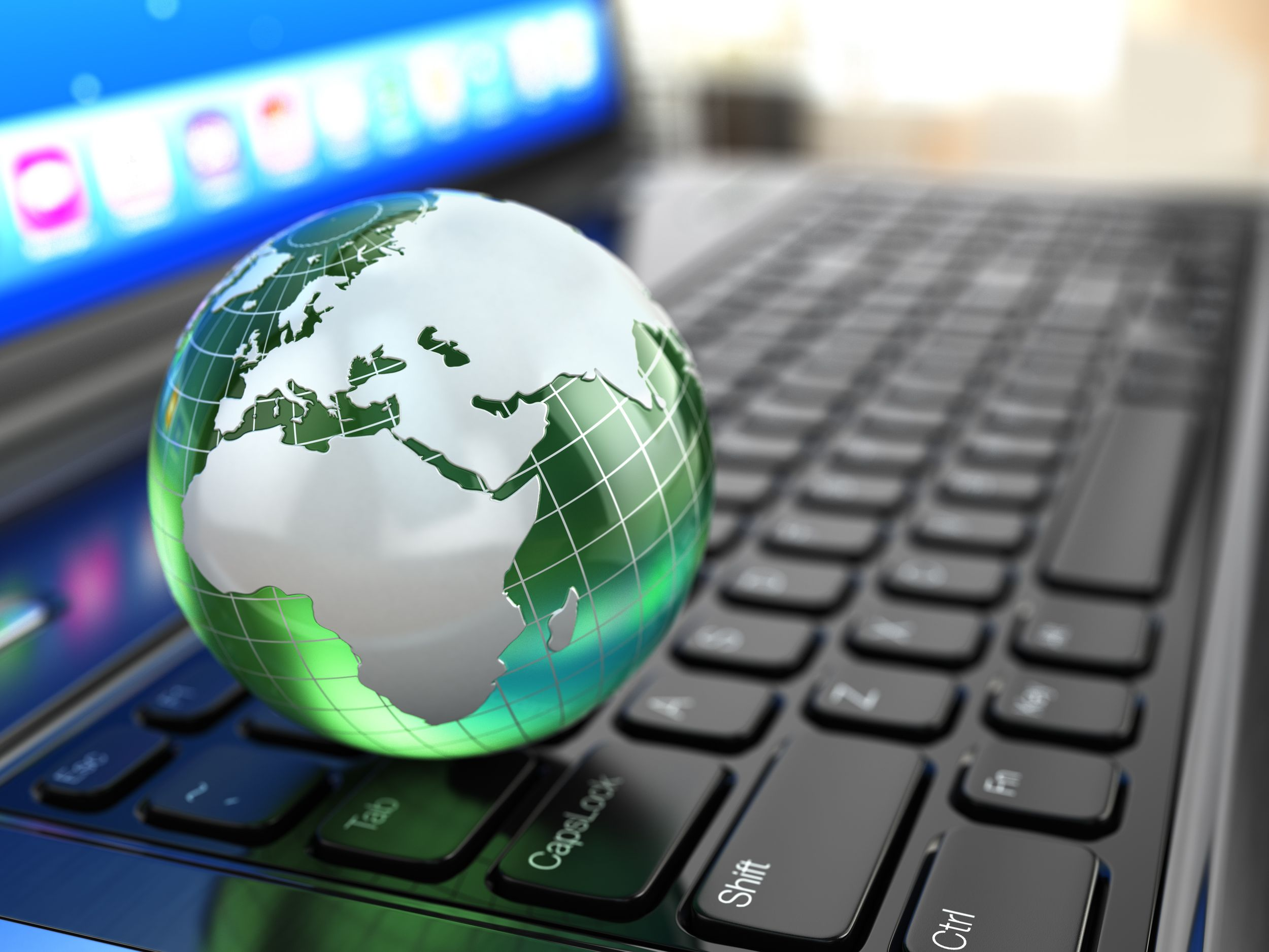Svetová komunikácia. Zemegula na klávesnici laptopu.