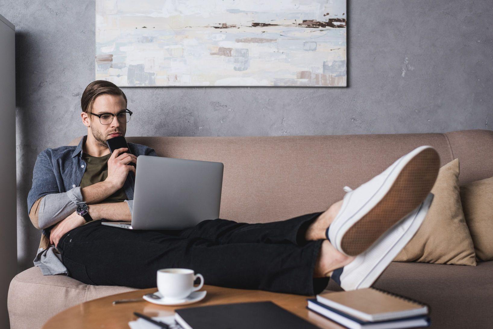 Mladý muž s nohami na stole a notebookom na kolenách pri káve pracuje z pohodlia domova.
